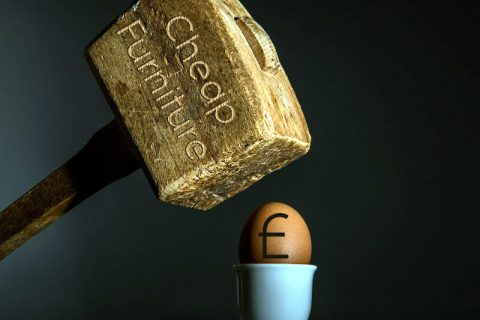 Mallet beating pound symbol on an egg.